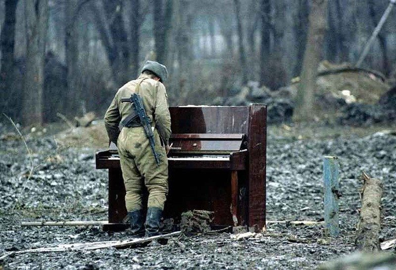 military plays an abandoned piano in the middle of the forest